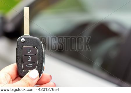 Close-up Of A New Modern Automobile Key In Woman's Hand On The Background Of A Silver Car. The Conce