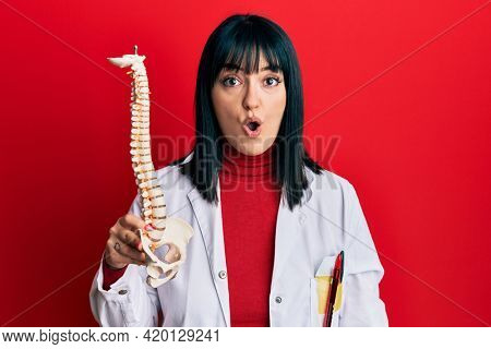 Young hispanic doctor woman holding anatomical model of spinal column scared and amazed with open mouth for surprise, disbelief face
