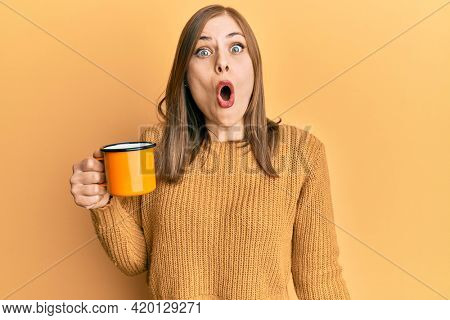 Beautiful caucasian woman drinking a cup coffee scared and amazed with open mouth for surprise, disbelief face