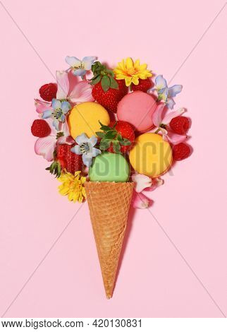 Delicious ice cream cone arrangement with macaroons, berries and flowers