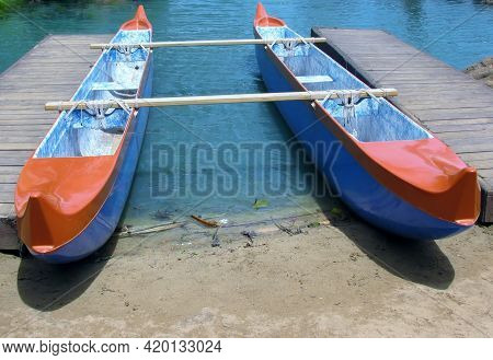 Double Hulled Canoe Moored At Jetty On Lake