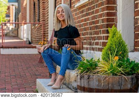 A gorgeous blonde model poses outdoors in an urban environment