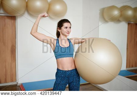 Positive Woman In Sportswear Holds A Fitness Ball And Shows Her Biceps
