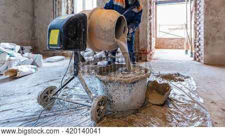 Worker Is Using The Electric Concrete Mixer In An Apartment Is Under Construction, Remodeling, Renov