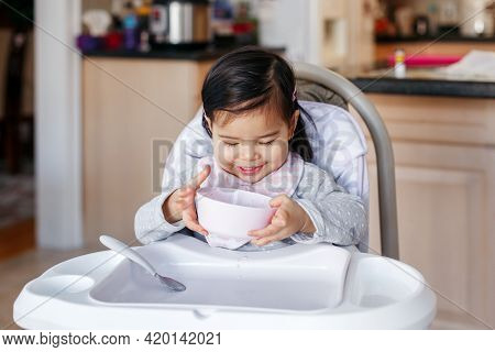 Cute Adorable Asian Chinese Kid Girl Sitting In High Chair Eating Soup With Spoon. Healthy Eating Fo