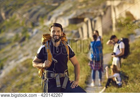 Handsome Young Man Standing On Hiking Trail And Looking At Camera With Friends In Blurred Background