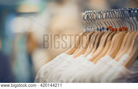 T-shirts On Hangers. Shopping In Store. Clothes On Hangers In Shop For Sale. Blur Background. Fashio