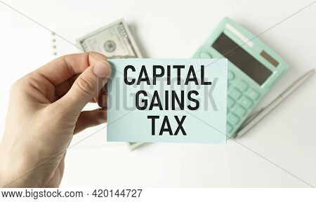 Closeup On Businessman Holding A Card With Text Capital Gains Tax, Business Concept Image With Soft