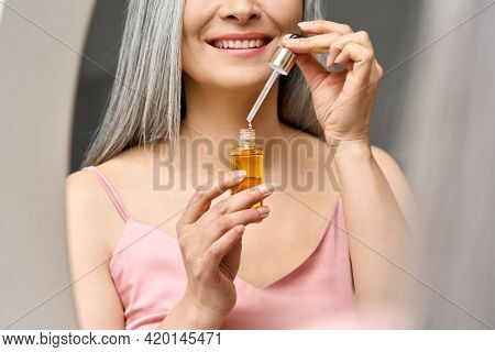 Closeup Cut Portrait Of Happy Smiling Senior Mature Older Asian Woman Holding Pipette And Bottle Wit