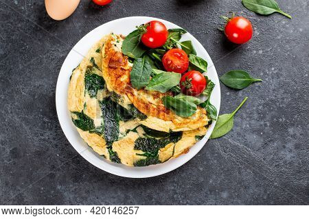 Green Omelet With Spinach, Tomato And Spices On White Plate. Frittata - Italian Omelet. Top View.