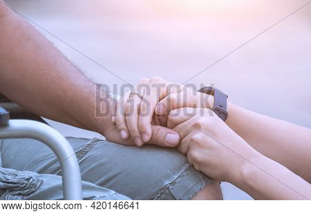 Close Up Image Of Woman Hands Holding Her Husband's Hand On Wheelchair During Rehabilitation For Enc