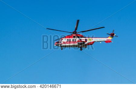 Red Rescue Helicopter Moving In Blue Sky. Rapid Medical Assistance Or Rescue By Helicopter: Kiev, Uk