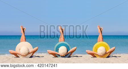 Three Young Girls On The Beach Wearing Straw Hats In The Colors Of The Flag Of Canary Islands. The C