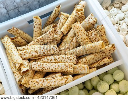 Frozen Thin Pancakes Sold By Weight In A Refrigerator Container On A Store Counter. Frozen Food Sale