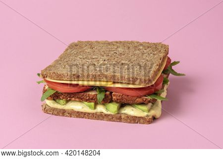 Vegan Sandwich Close-up On A Pink Table. Wholemeal Bread Sandwich With Vegan Cheese, Tofu, Avocado,