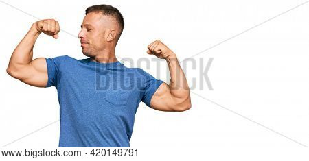 Handsome muscle man wearing casual clothes showing arms muscles smiling proud. fitness concept.