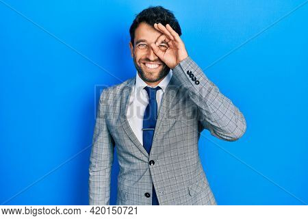 Handsome man with beard wearing business suit and tie doing ok gesture with hand smiling, eye looking through fingers with happy face.