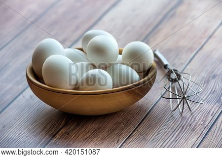 Wooden Bowl With White Chicken Eggs And Steel Whisk On Wood Table. Qhite Eggs In Bowl On Wood Backgr