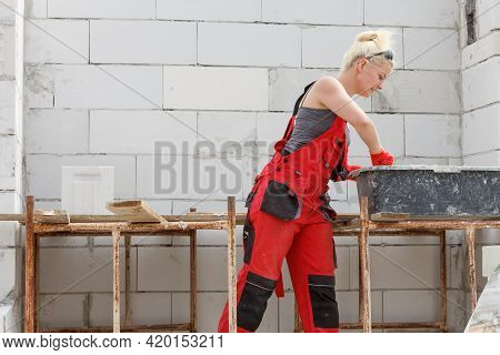 Woman Wearing Dungarees Working On Construction Site Of Her Home. Mixing Cement In Bowl Preparing Mo