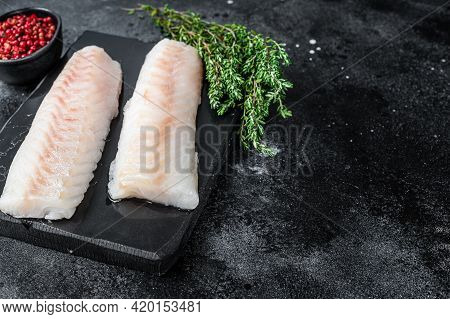 Raw Cod Loin Fillet Fish On Marble Board. Black Background. Top View. Copy Space