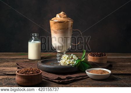 Korean Dalgona Coffee With Foam And Ice On A Brown Background. Side View, Horizontal. An Invigoratin