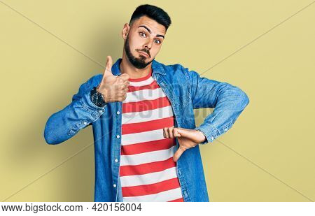 Young hispanic man with beard wearing casual denim jacket doing thumbs up and down, disagreement and agreement expression. crazy conflict