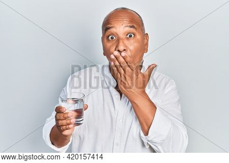 Middle age latin man drinking glass of water covering mouth with hand, shocked and afraid for mistake. surprised expression