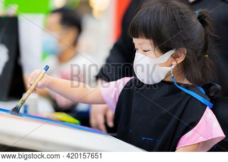 Cute Girl Wearing A 3d Surgical Face Mask Is Taking Art Classes In Classroom. Child Make Crafts With