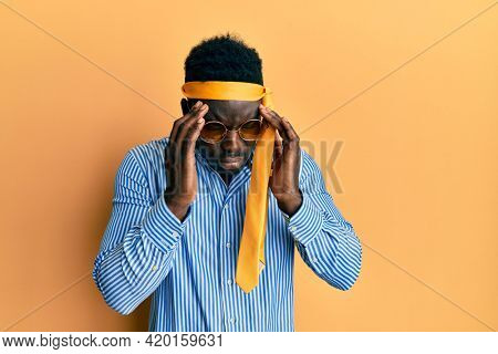 Handsome black man drunk wearing tie over head and sunglasses with hand on head for pain in head because stress. suffering migraine.
