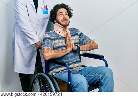 Handsome hispanic man sitting on wheelchair wearing neck collar begging and praying with hands together with hope expression on face very emotional and worried. begging.