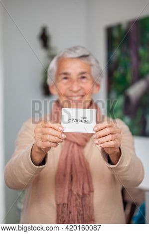 Senior Woman At Her Home Holding Her Vaccination Certificate After Getting The Covid-19 Vaccine At A