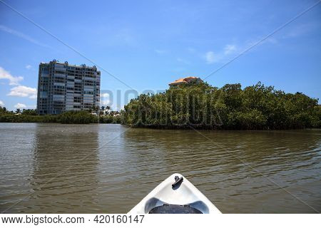 Kayak Forges Its Way Through The Residential Waterways Near Clam Pass In Naples, Florida