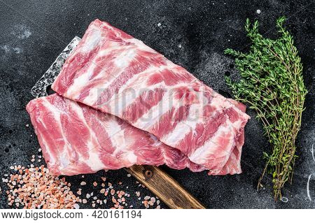 Uncooked Raw Pork Spare Ribs On Butcher Meat Cleaver. Black Background. Top View