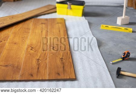 Laminate floor background texture and tools. Wooden laminate floor plank with copy space