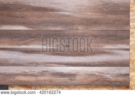 Laminate floor on wood osb background texture. Wooden laminate floor and chipboard background with copy space