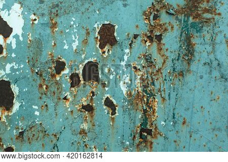 Texture of a worn metal surface with rust and traces of old paint.