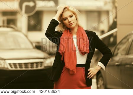 Young fashion business woman walking on city street Stylish female model in black suit blazer and red scarf