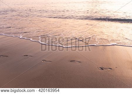 Footprints In The Sand By The Sea. In The Light Of The Sunset, The Footprints Follow The Sand Along