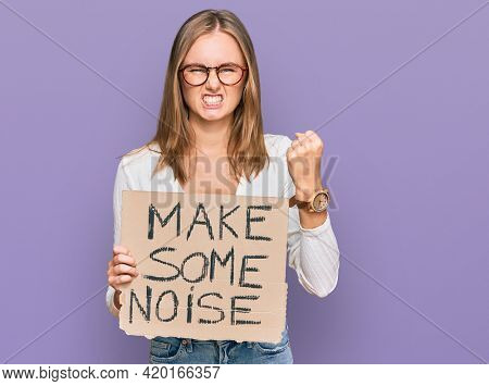 Beautiful blonde woman holding make some noise banner annoyed and frustrated shouting with anger, yelling crazy with anger and hand raised