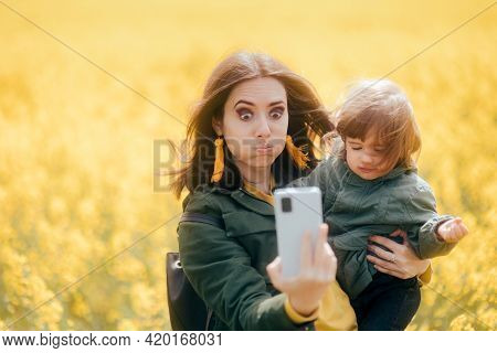 Clumsy Mom And Upset Daughter Taking Selfies In Rapeseed Field