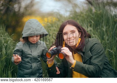 Mother And Daughter Observing Nature With Binoculars