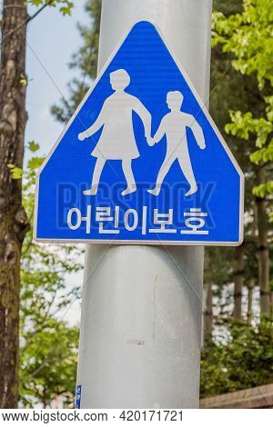 Sign Of Two People Holding Hands With Korean Language That Says