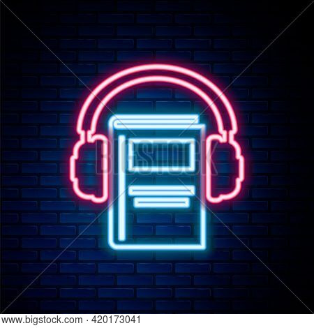 Glowing Neon Line Audio Book Icon Isolated On Brick Wall Background. Book With Headphones. Audio Gui