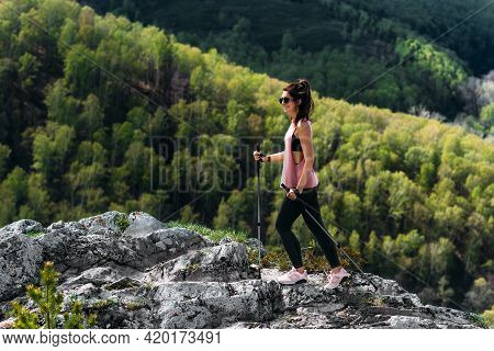 Hiking In The Mountains. A Man Is Engaged In Nordic Walking In The Mountains. Tourist In The Mountai