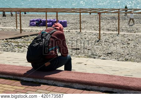 A Lone Figure Of A Young Man With A Backpack On His Back, Sitting On The Sparsely Populated Embankme