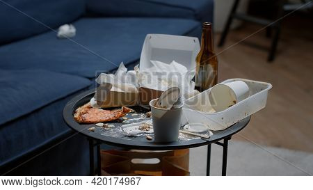 Close Up Of Leftover Food On Table In Empty Messy Living Room