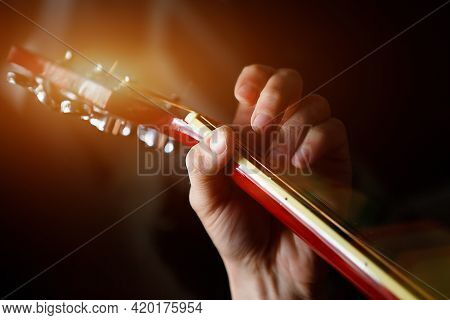 A Man\'s Hand On The Fretboard Of A Guitar Runs His Fingers Through The Strings And Clamps The Chord