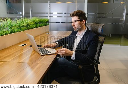 Young Business Man In Office Work Online On Laptop Solve Business Problem. Pensive Businessman Use C