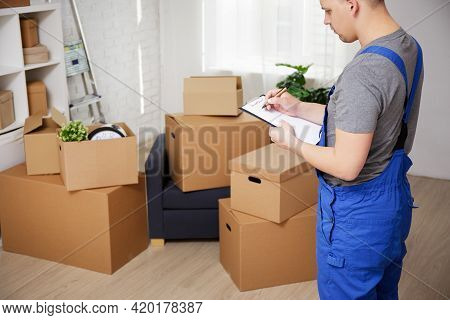 Delivery Or Moving Day Concept - Loader Looking On Cardboard Boxes And Writing Something On Clipboar