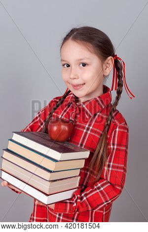 Little Funny Girl In Shirt With Books. Isolated On White Background. Baby Girl In School. The Child